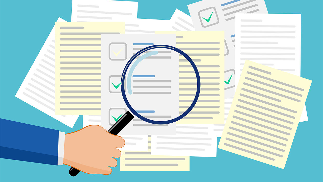 A magnifying glass looking at papers to suggest the idea of verification.