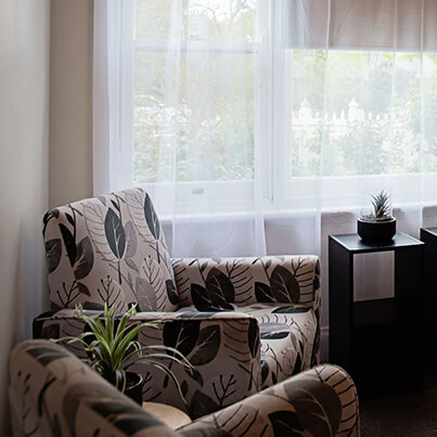 Two chairs, indoor plants and sunlight coming through the window in the clinic room at Sevens Creek Psychology Euroa