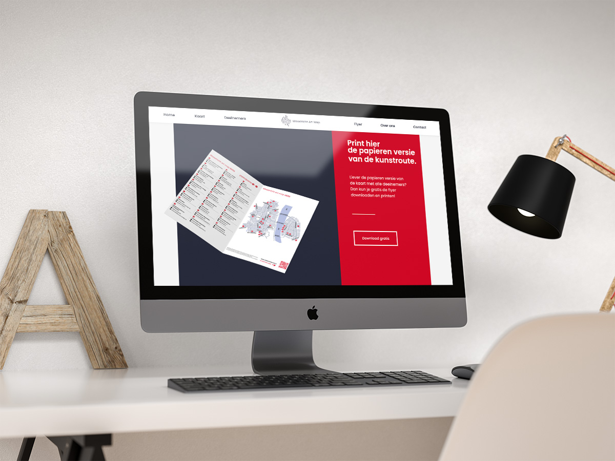 An iMac on a desk displaying the website of Maastricht kunst