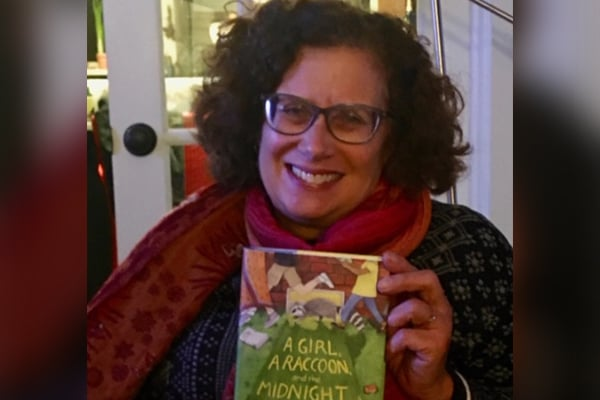 uthor Karen Romano Young holding up her latest book, A Girl, A Raccoon, and the Midnight Moon