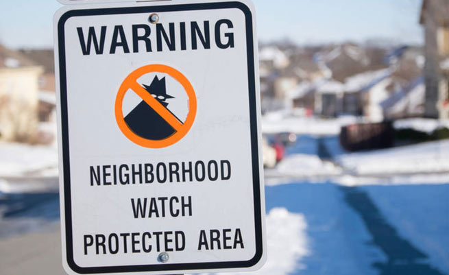 Street sign reading: Warning Neighborhood Watch Protected Area.