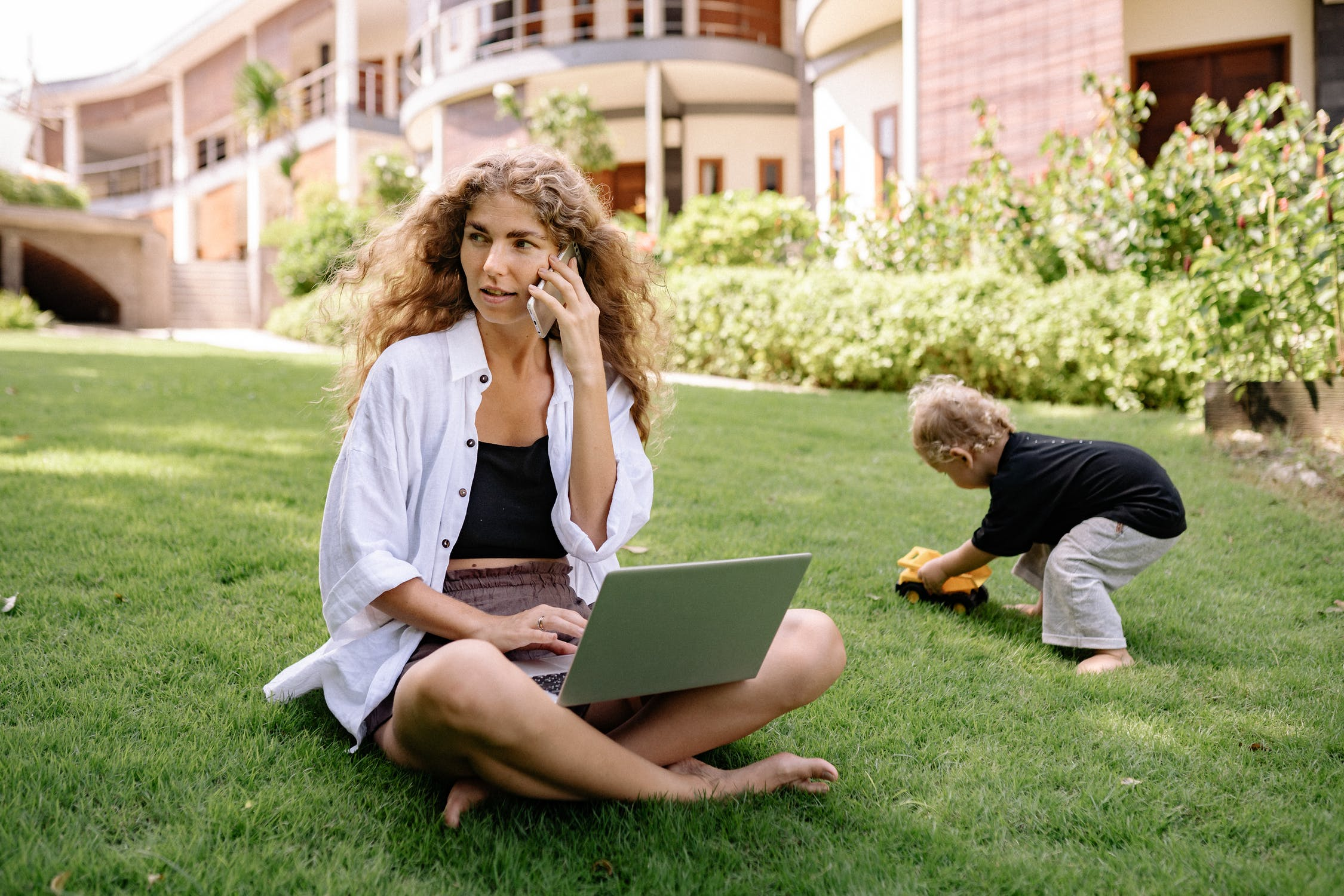 Woman sitting with her son on a lawn. She has a laptop in her lap and she is on the phone looking around her in a concerned way.