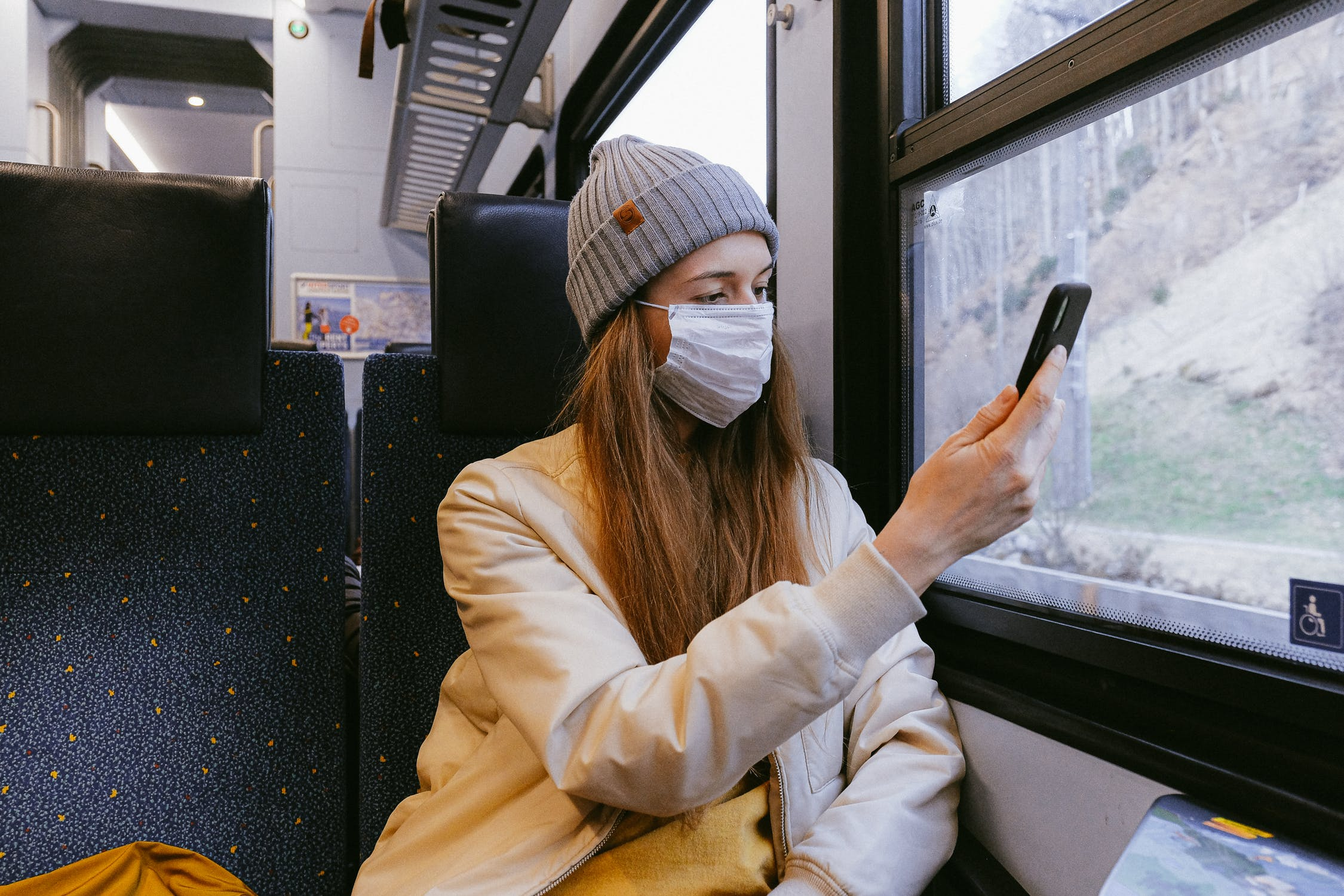 A woman wearing a jacket, beanie, and surgical face mask on a train pointing her phone toward the window.