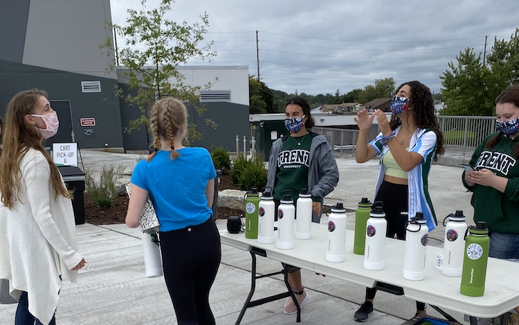 Students managing a giveaway table outside Trent University Durham GTA.