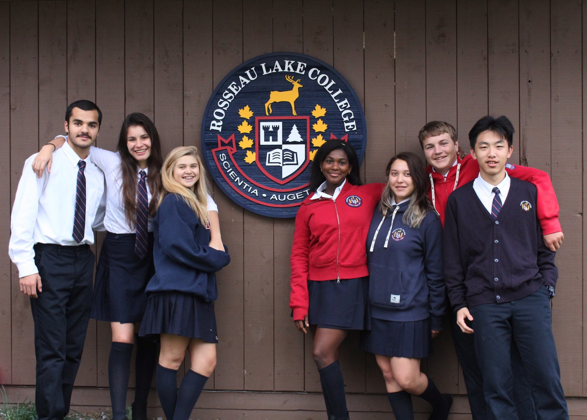 A group of smiling students poses in front of the RLC dining hall logo.
