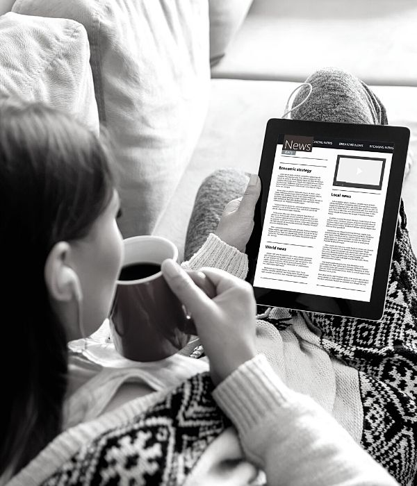image of a woman reading the news on her tablet