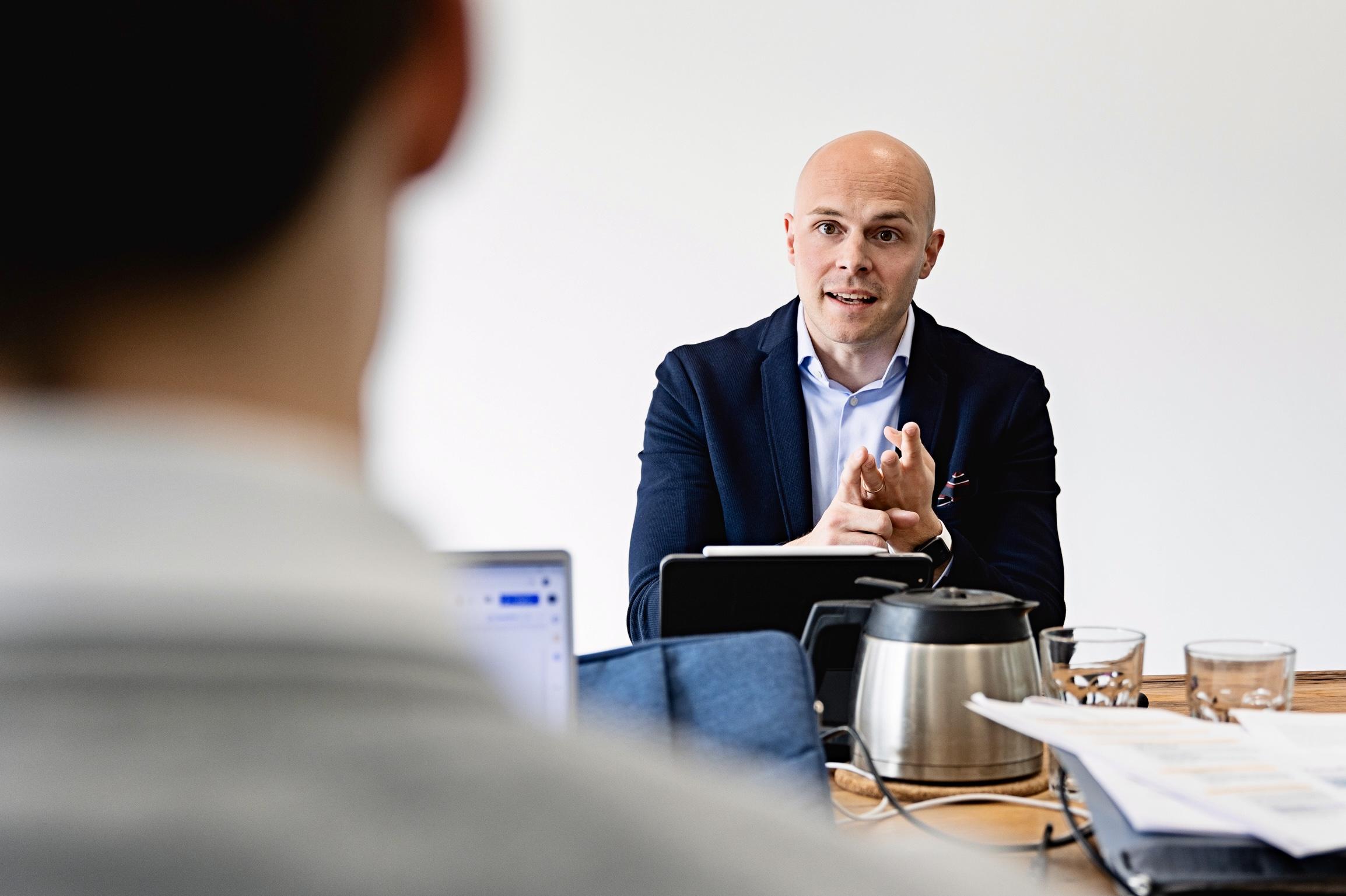 Ein Bild von Arne Böhm wie er jemanden am Tisch etwas erklärt
