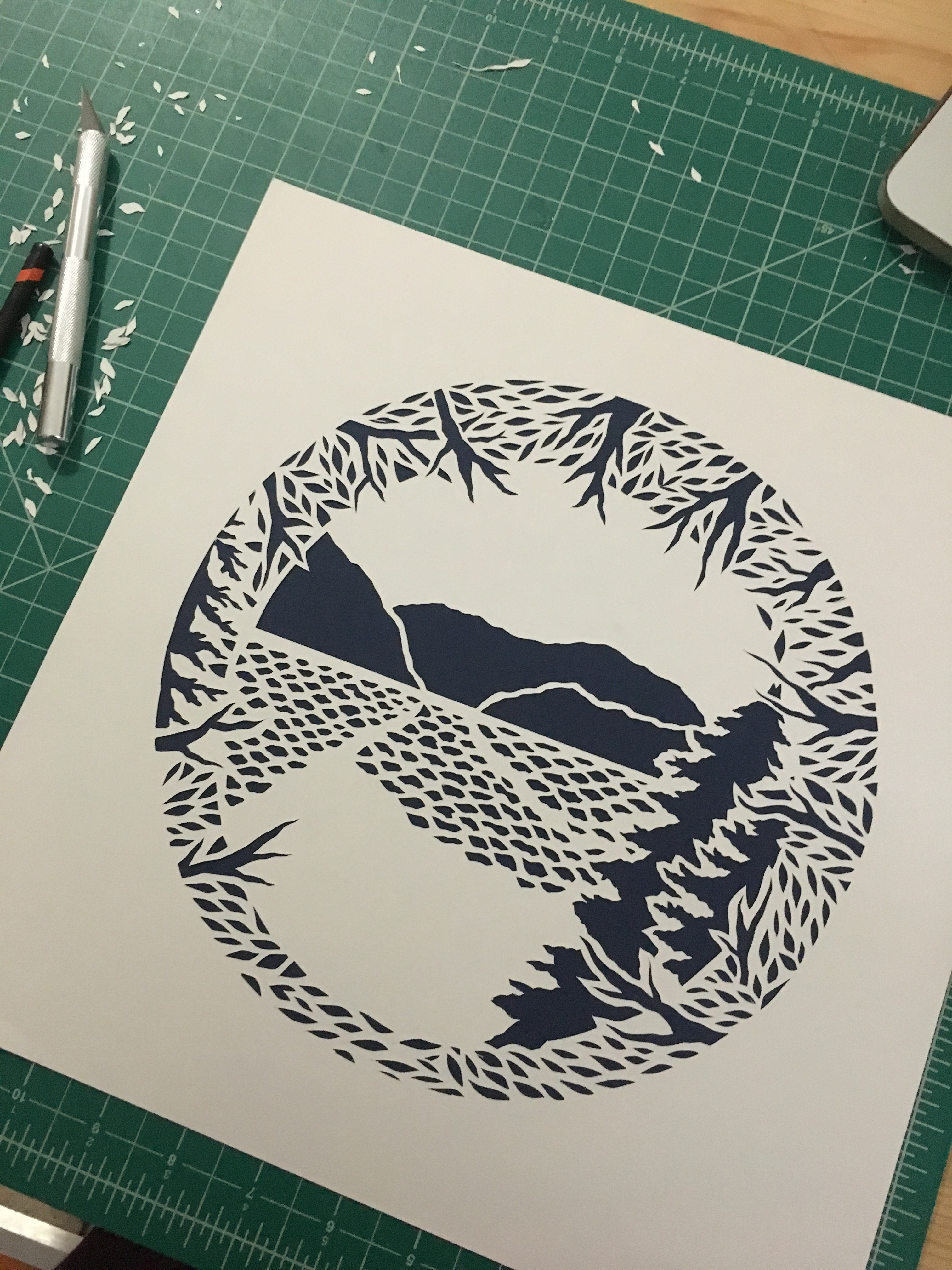 ocean and mountain scene by cutting forms out of one paper