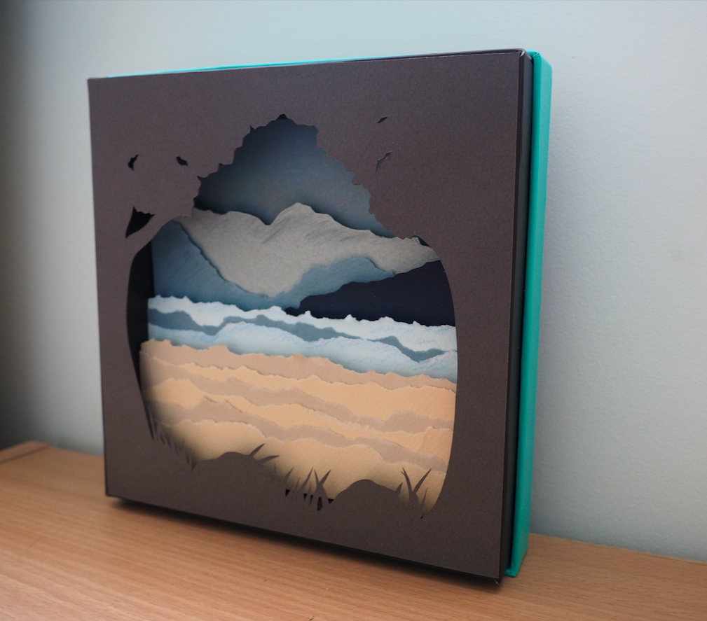 ocean scene created by adding layers of paper to create sand, ocean and mountains