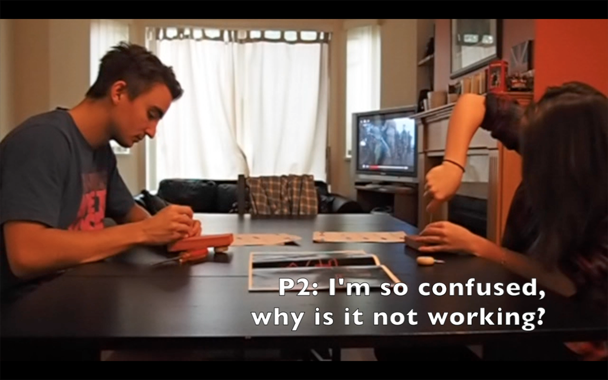 Photo of two people trying to complete the task. The person on the right is saying that they cannot do it