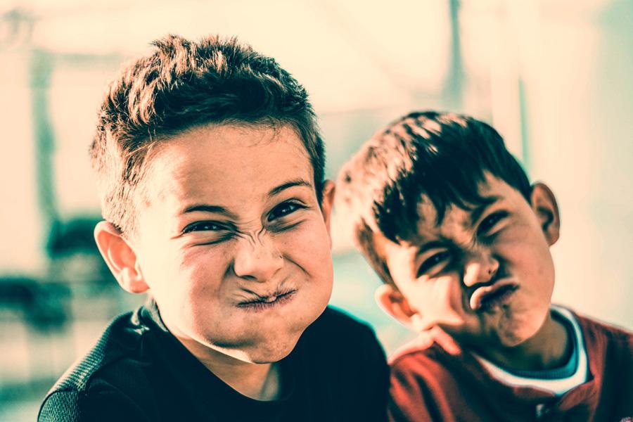 Twee jongens trekken gekke bekken richting de camera.
