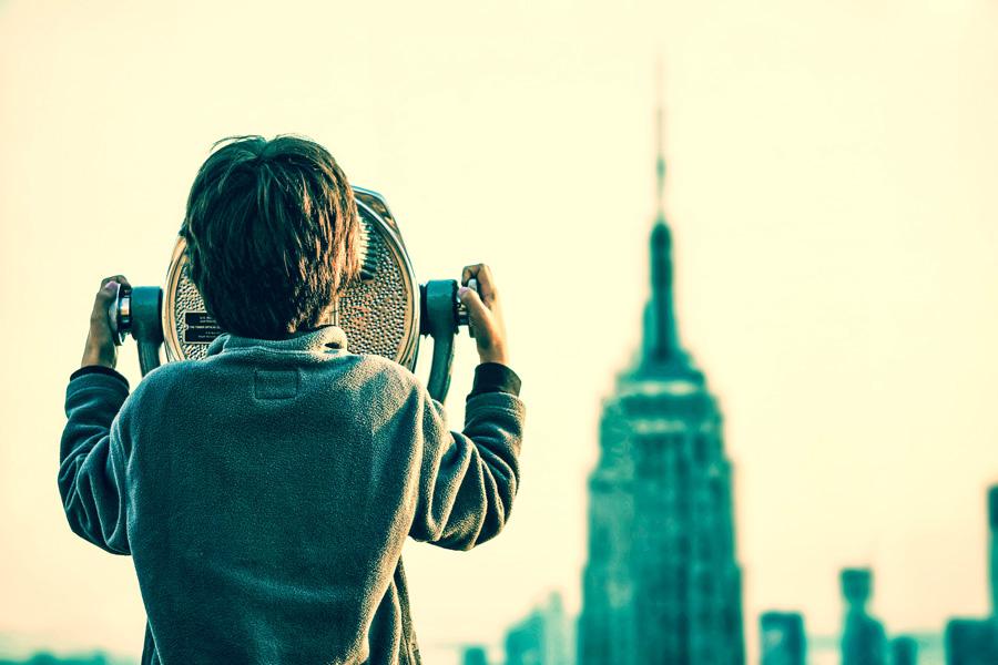 Een jongen bekijkt met een verrekijker naar een stad vol met wolkenkrabbers.