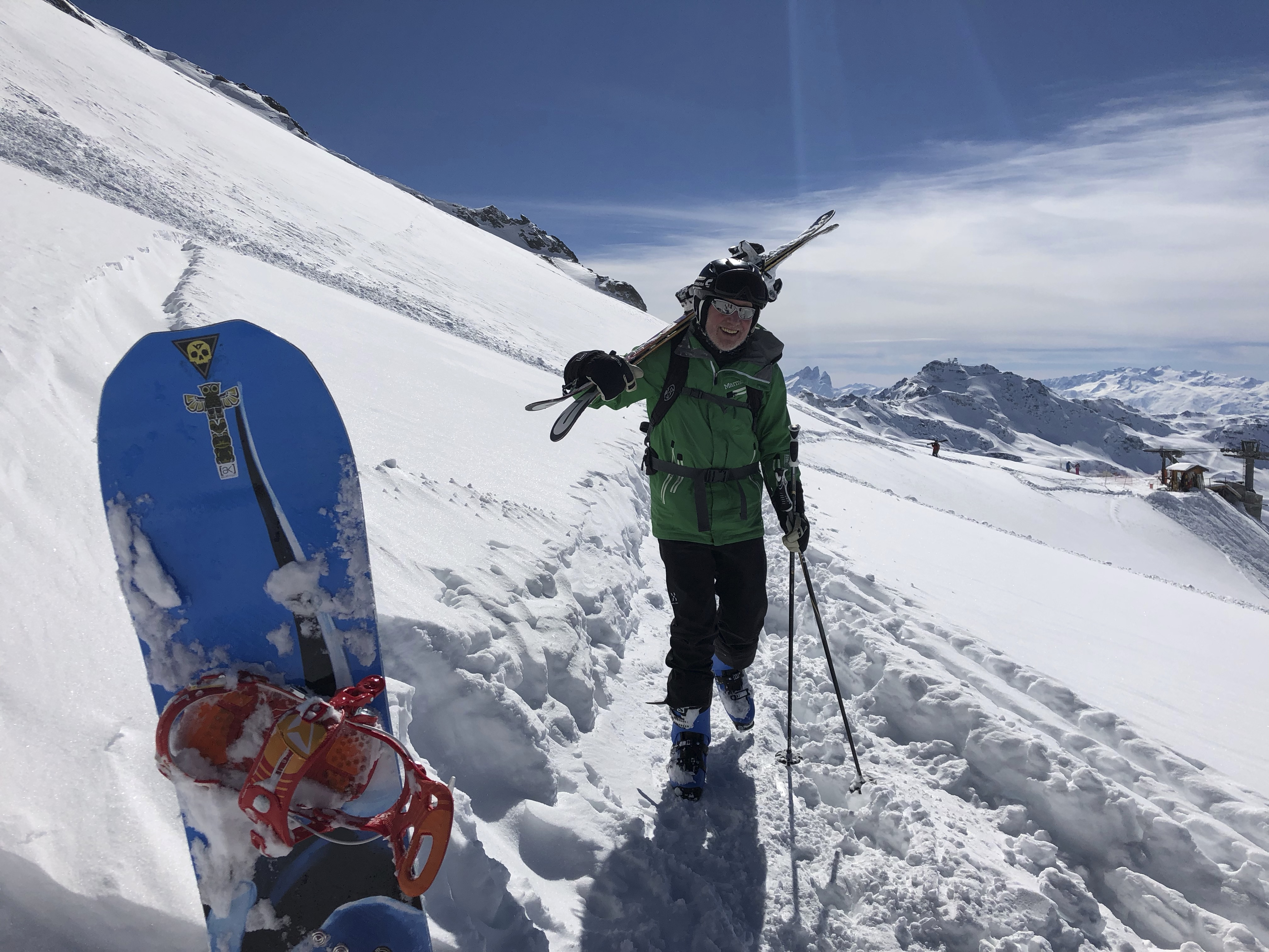 A FSCer skier in carrying his skies.