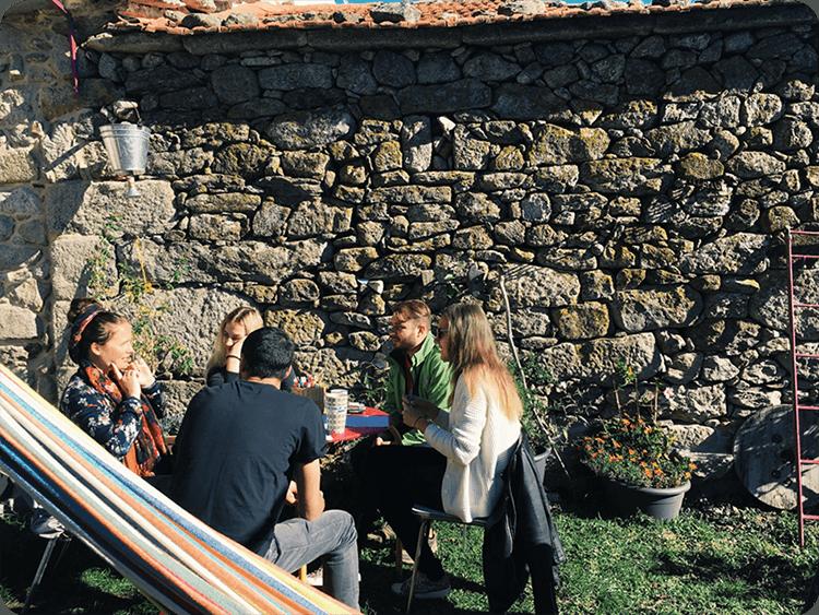 Digital nomads having breakfast in the garden near the stone house
