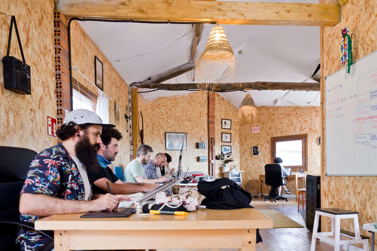 Inside of a coworking space in Sende. Creatives are sitting at different desks and working on their own projects.