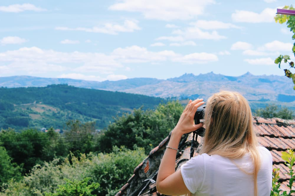 A girl looking over the mountains with binoculars.