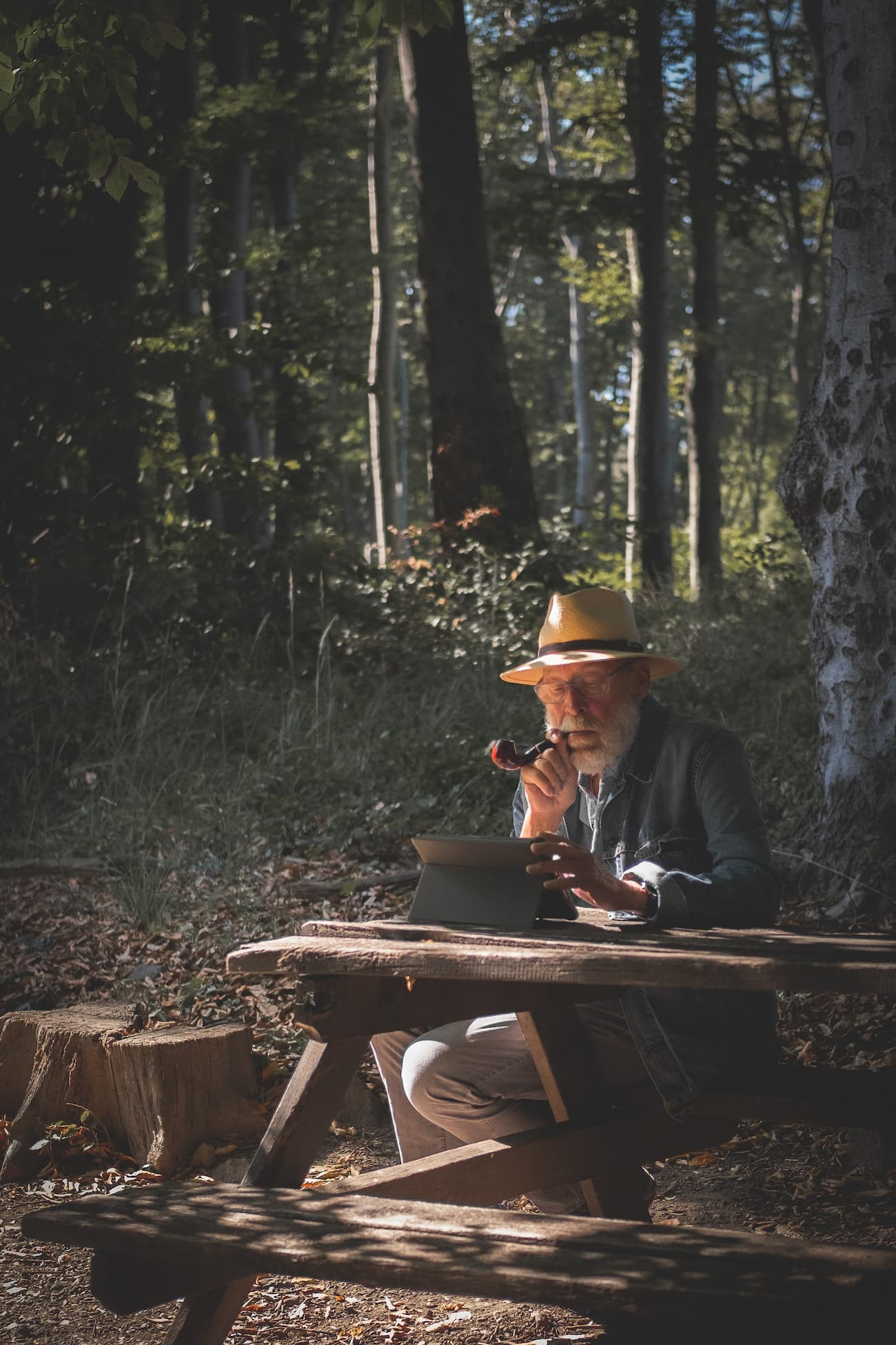 Old man with an ipad sitting in the forest
