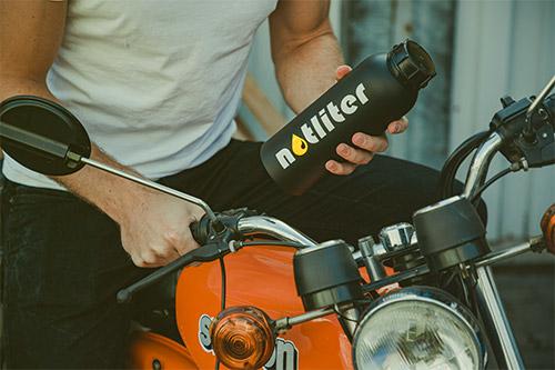 Mann auf Motorrad hält notliter Flasche in der Hand