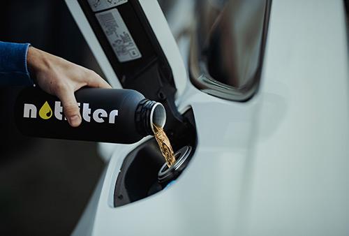 Bild zeigt wie Benzin in der notliter Flasche in einen Autotank gefuellt wird