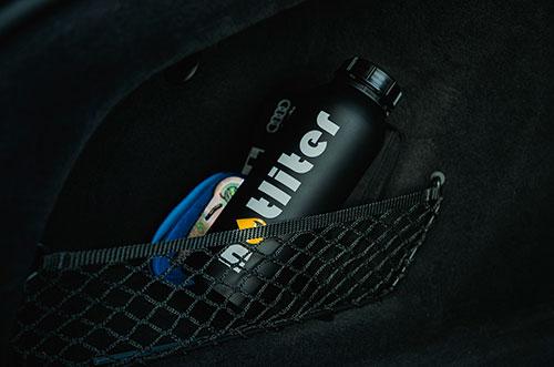 Bild zeigt notliter Flasche verstaut im Kofferraum eines Autos