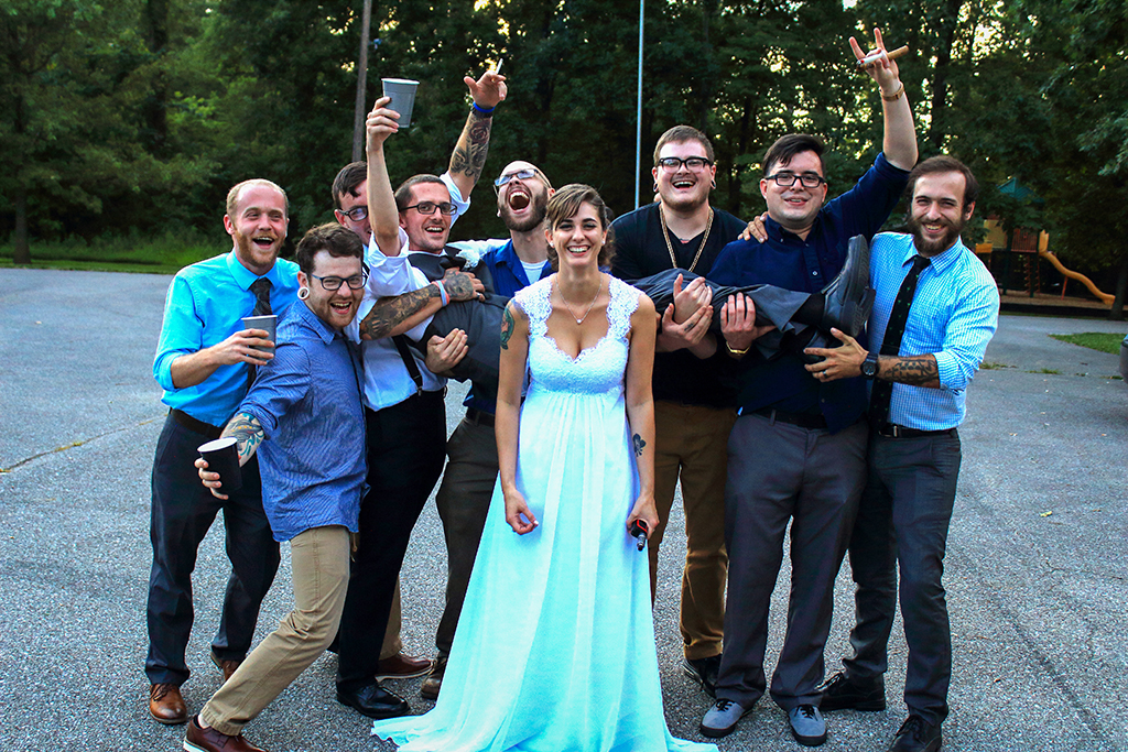 Image of wedding party and friends. The groom is laying across his friends arms while the bride is standing in front