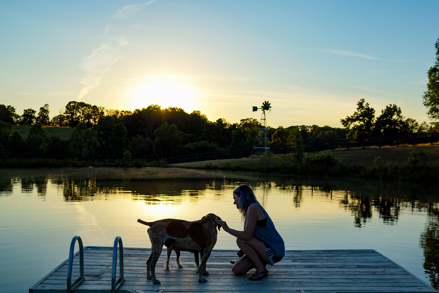 Image of a woman and a dog on a dock