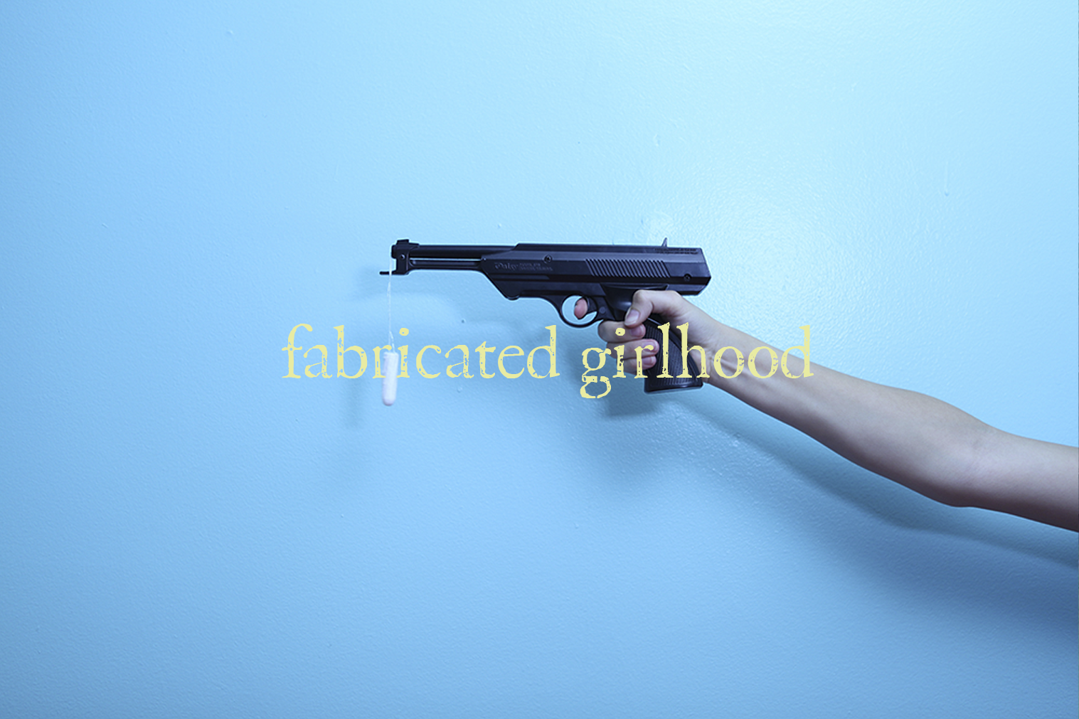 "A photo of a prop gun with a tampon handing out of the barrel with text overlaid ""fabricated girlhood"""