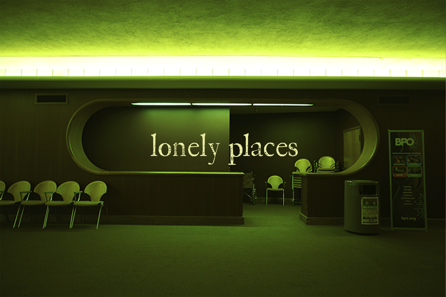 "A photo of a concert hall lobby with text overlaid ""lonely places"""