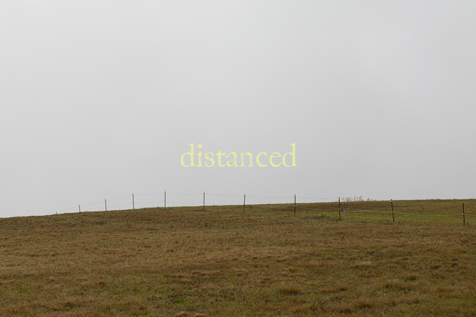 "A photo of an empty field with text overlaid ""distanced"""
