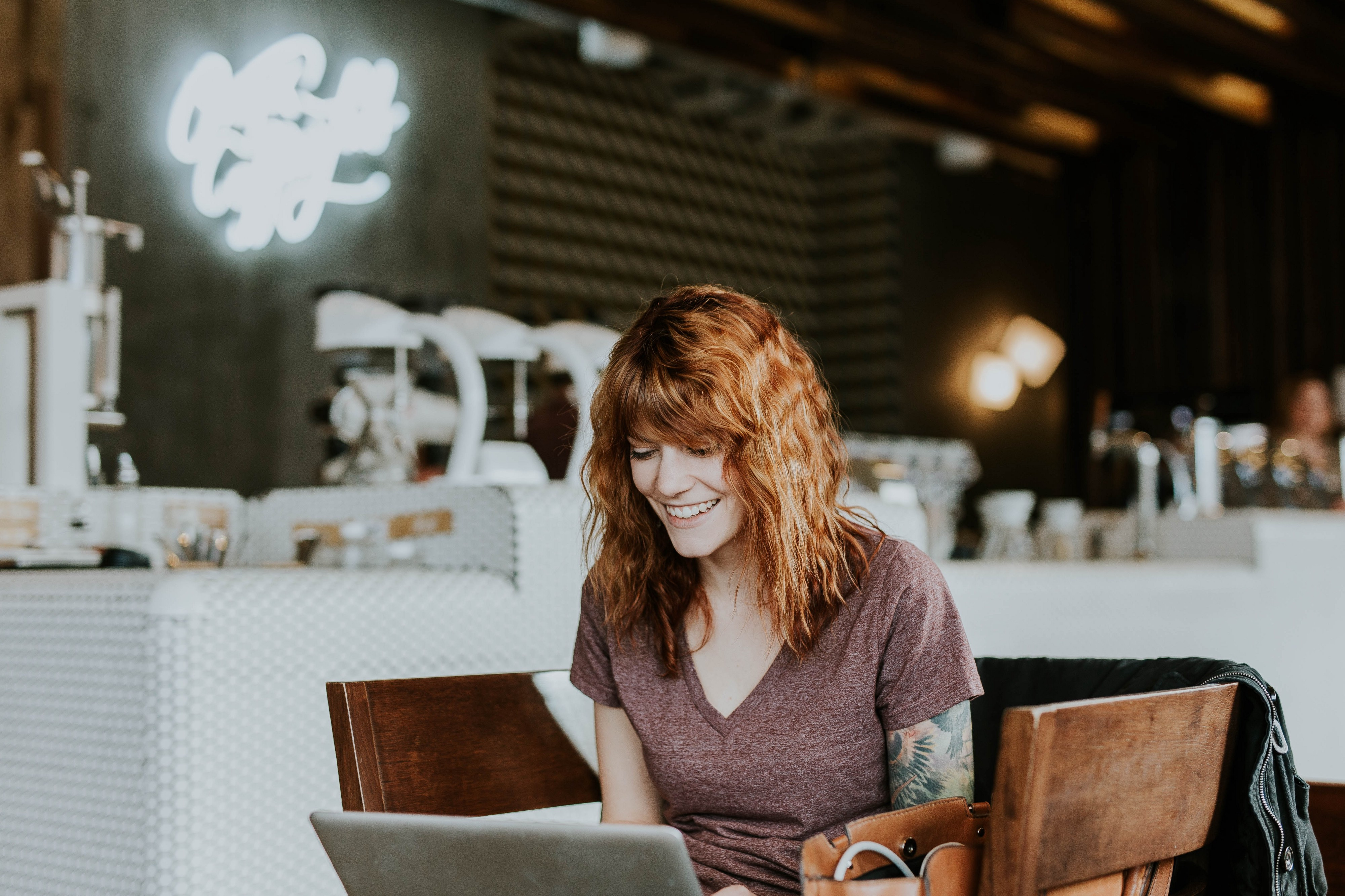 A woman smiles at her laptop at a cafe. Remote companies have a value-based culture.