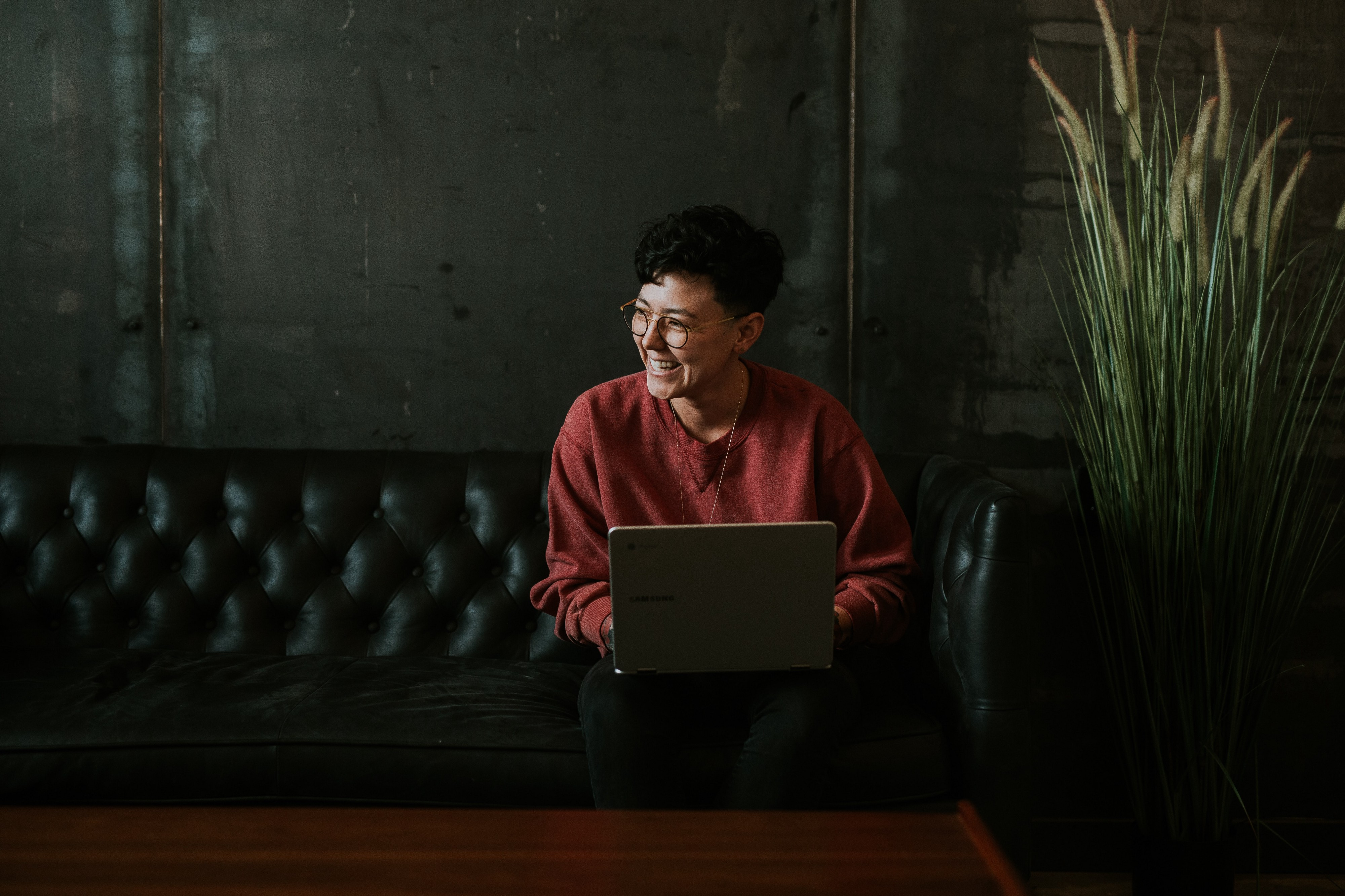 A remote worker smiles on a leather couch. Always assume good intent while communicating remotely.