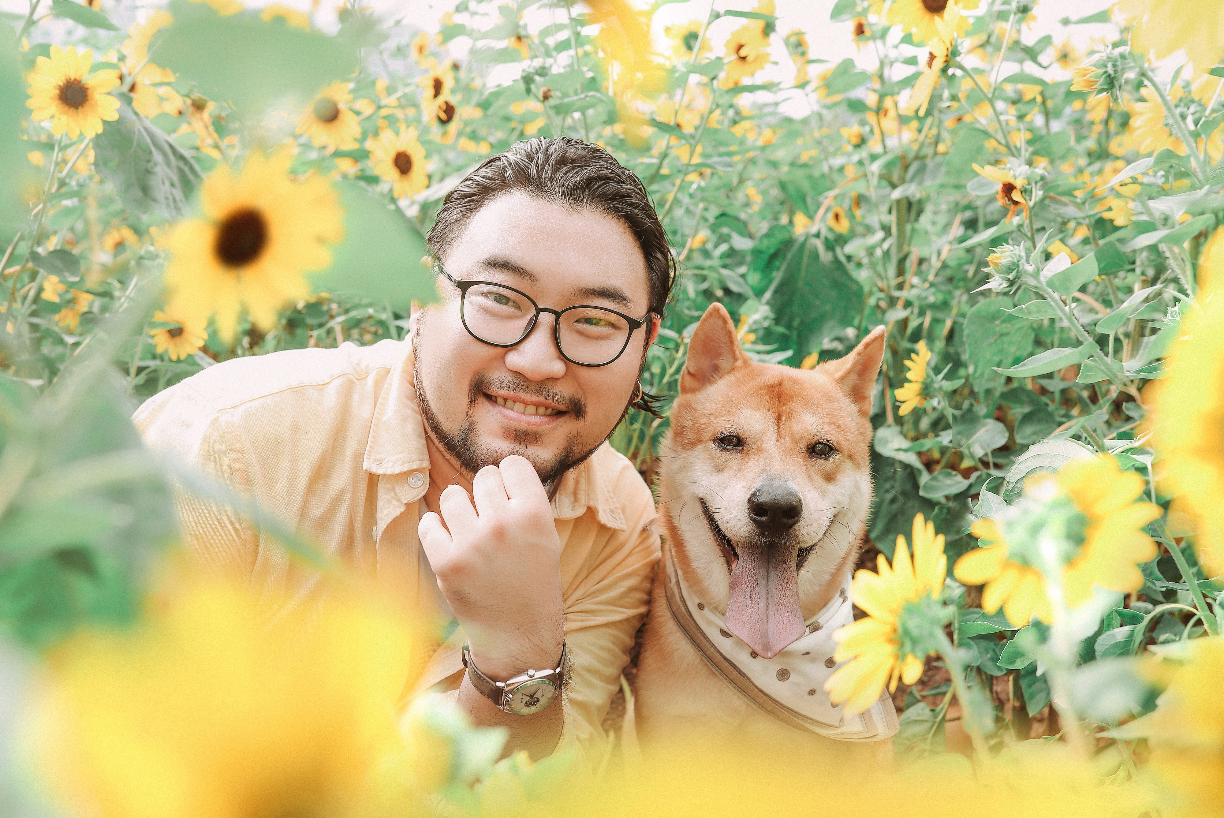 A man poses with his dog in a sunflower patch. Trust is crucial for remote teams.