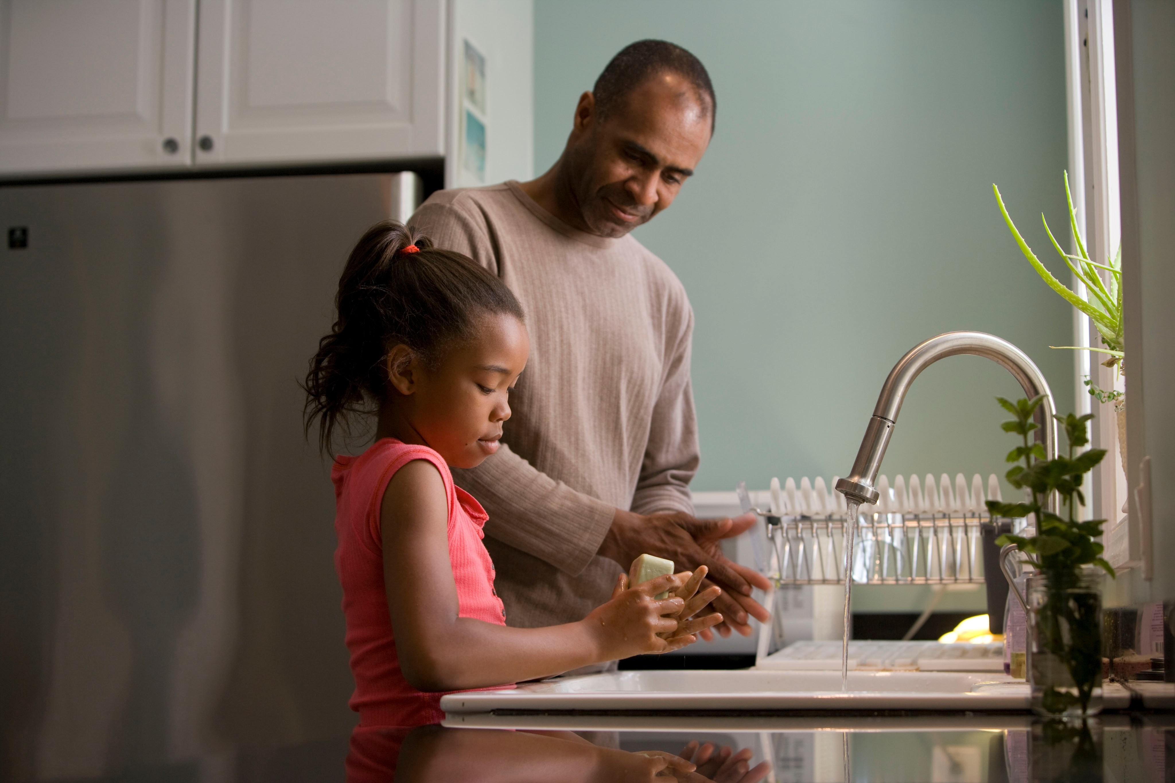 A man washes hands with his daughter. Value-based cultures allow people to spend time with their families.