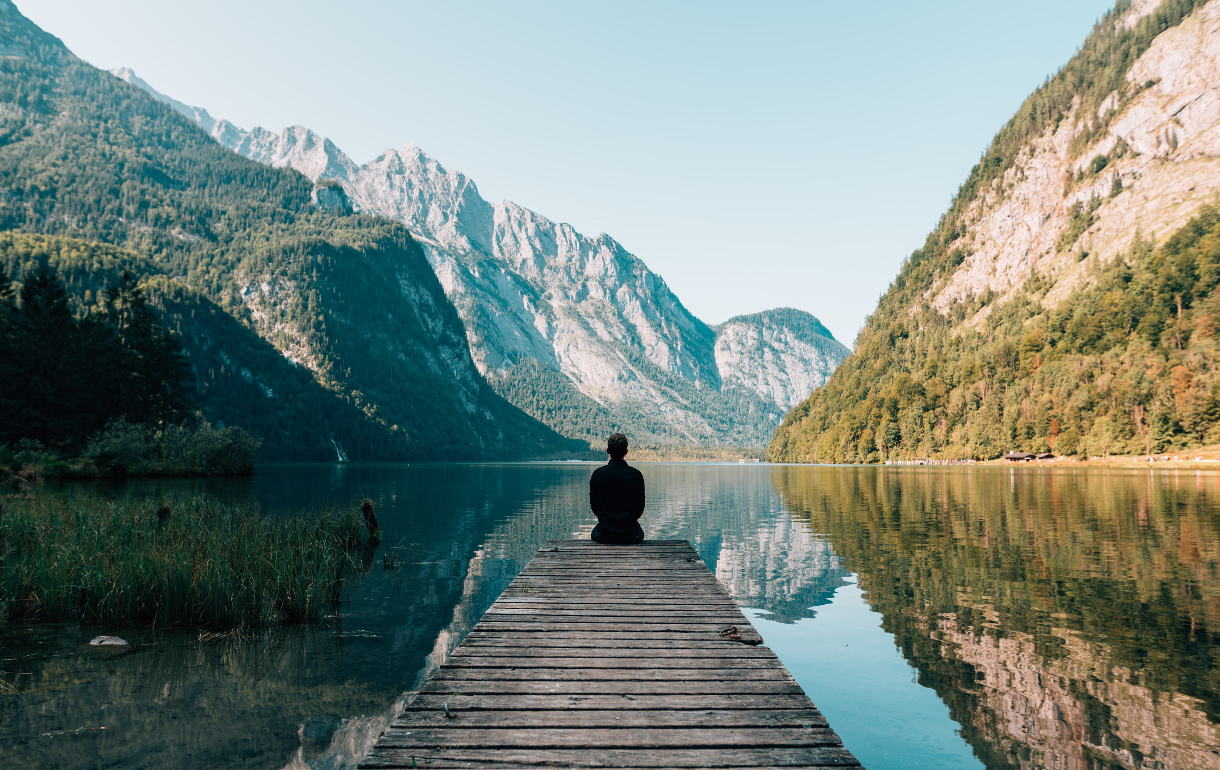 A remote manager sits in front of a gorgeous mountain lake. He is taking paid time off, thanks to his fantastic company culture.