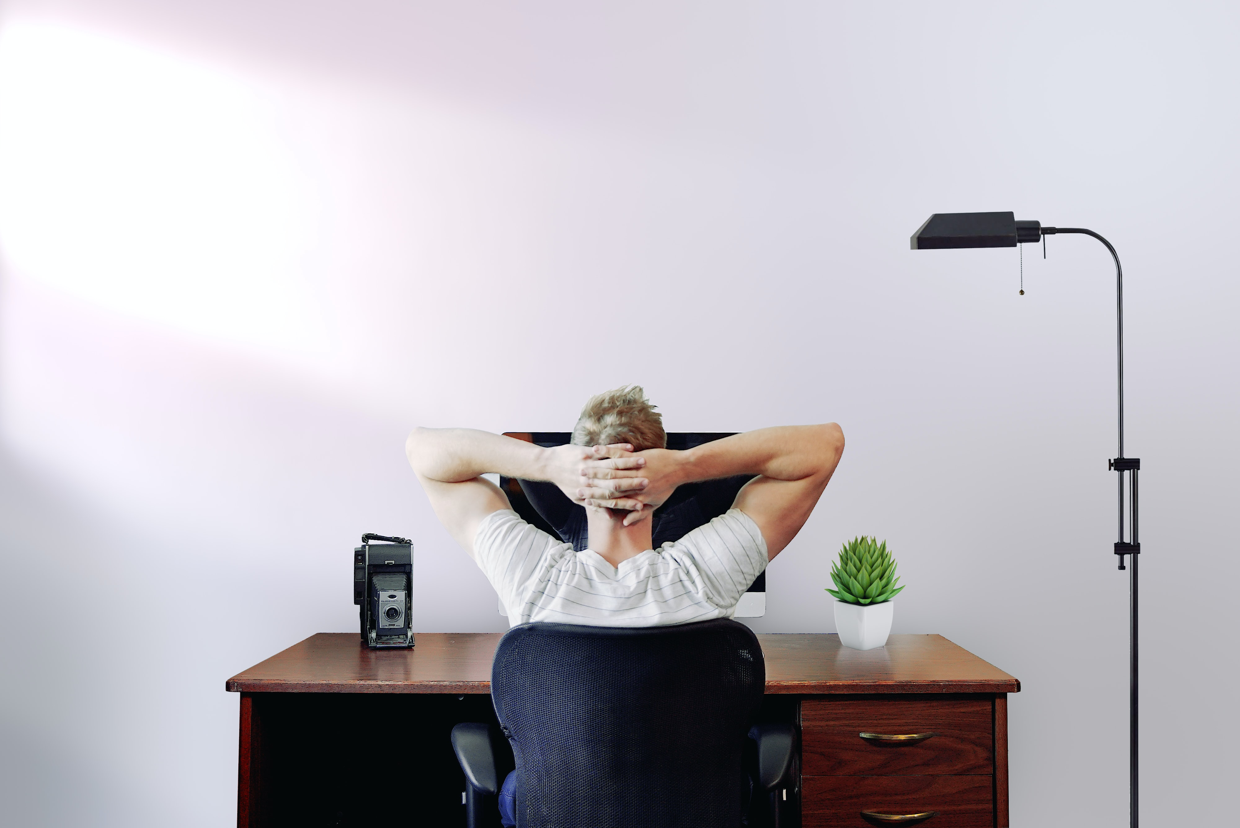 Trust is fundamental while managing remote teams. This image shows a man relaxing in front of his computer in front of a white wall.