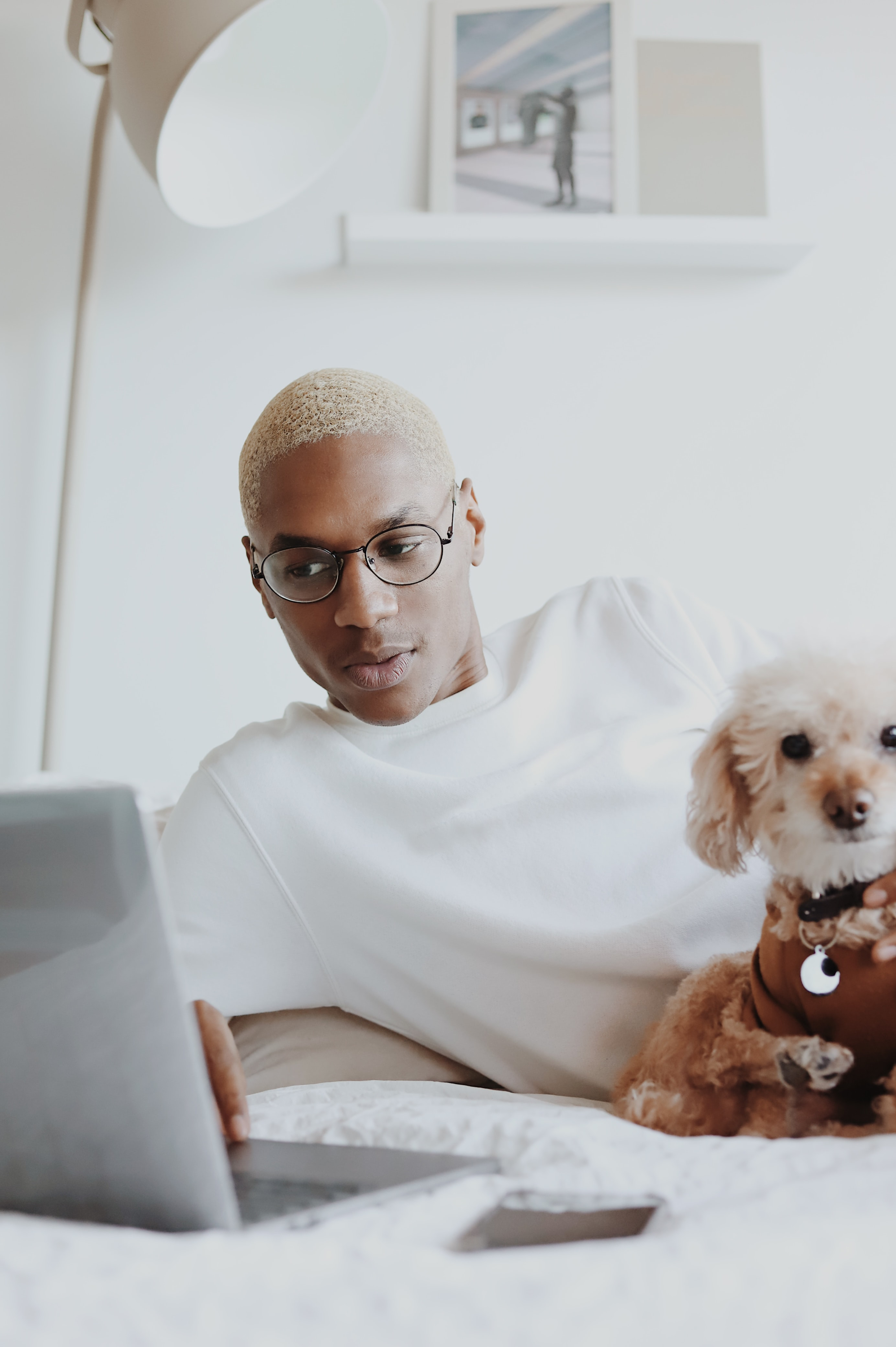 A man in white and his dog look at a laptop. He looks focused on his Zoom meetings.