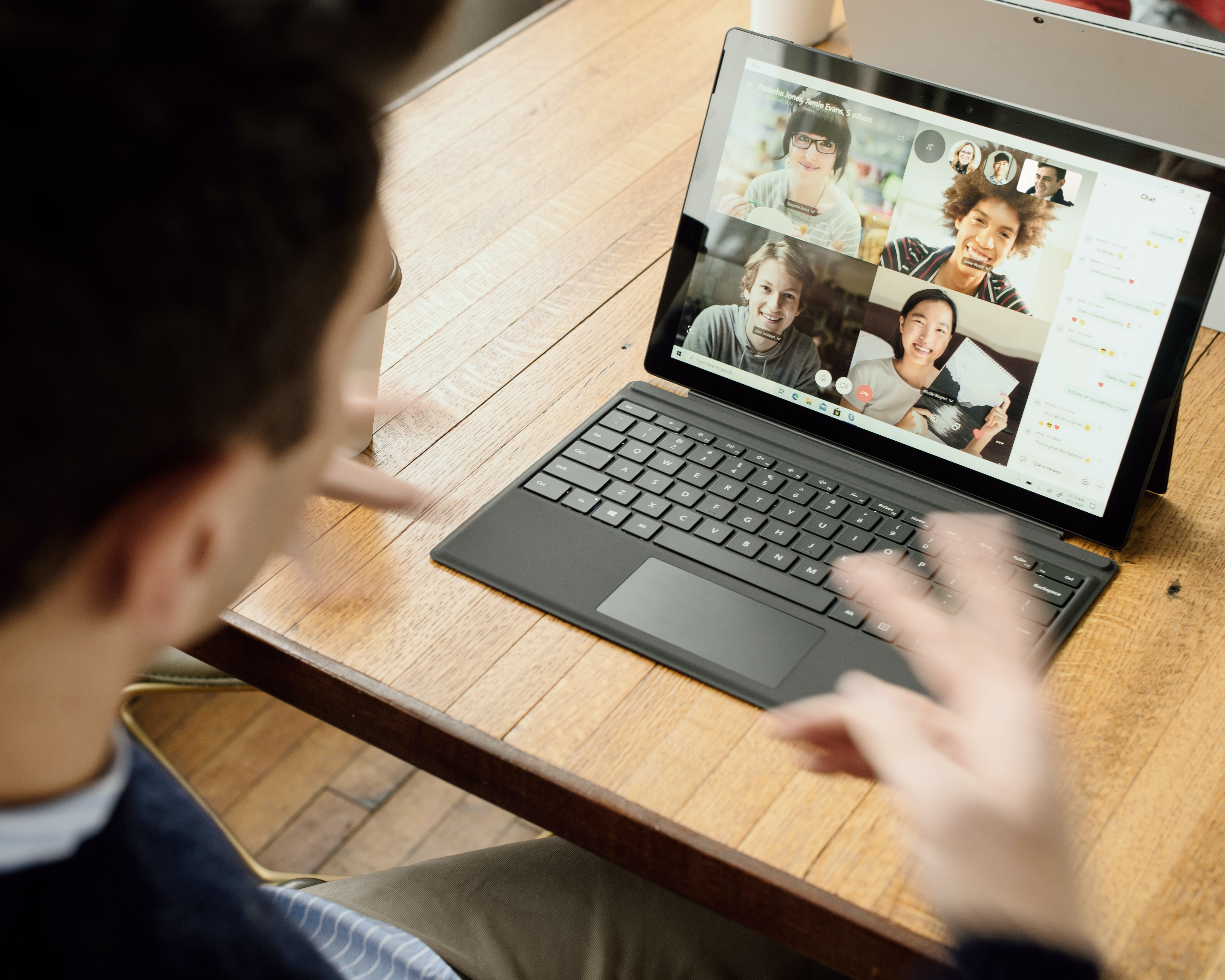 A man gestures to his remote teammates on a Microsoft Teams meeting.