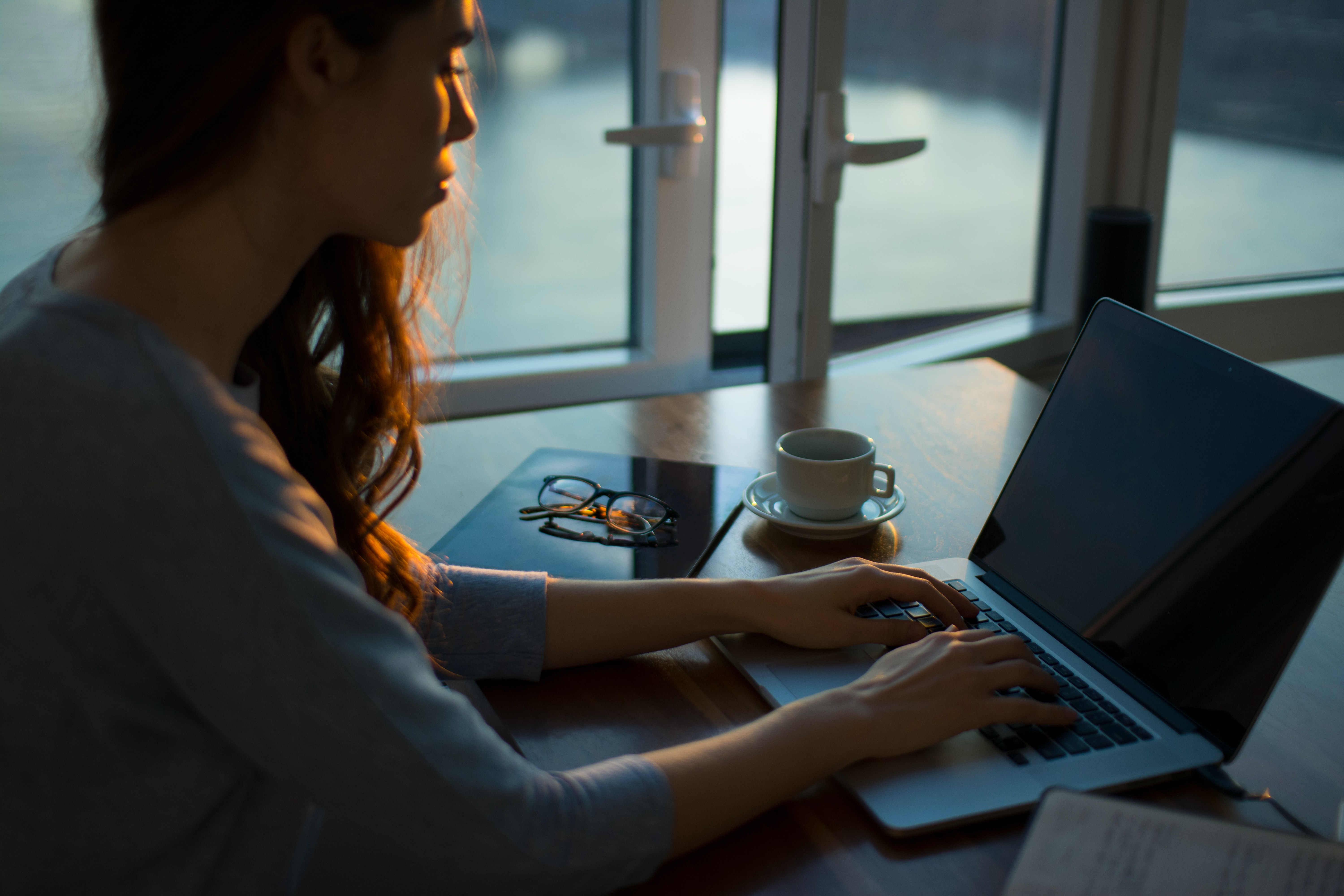 A woman sits at her desk at dawn. She's reflecting on her team and thinking of ways to recognize a coworker.