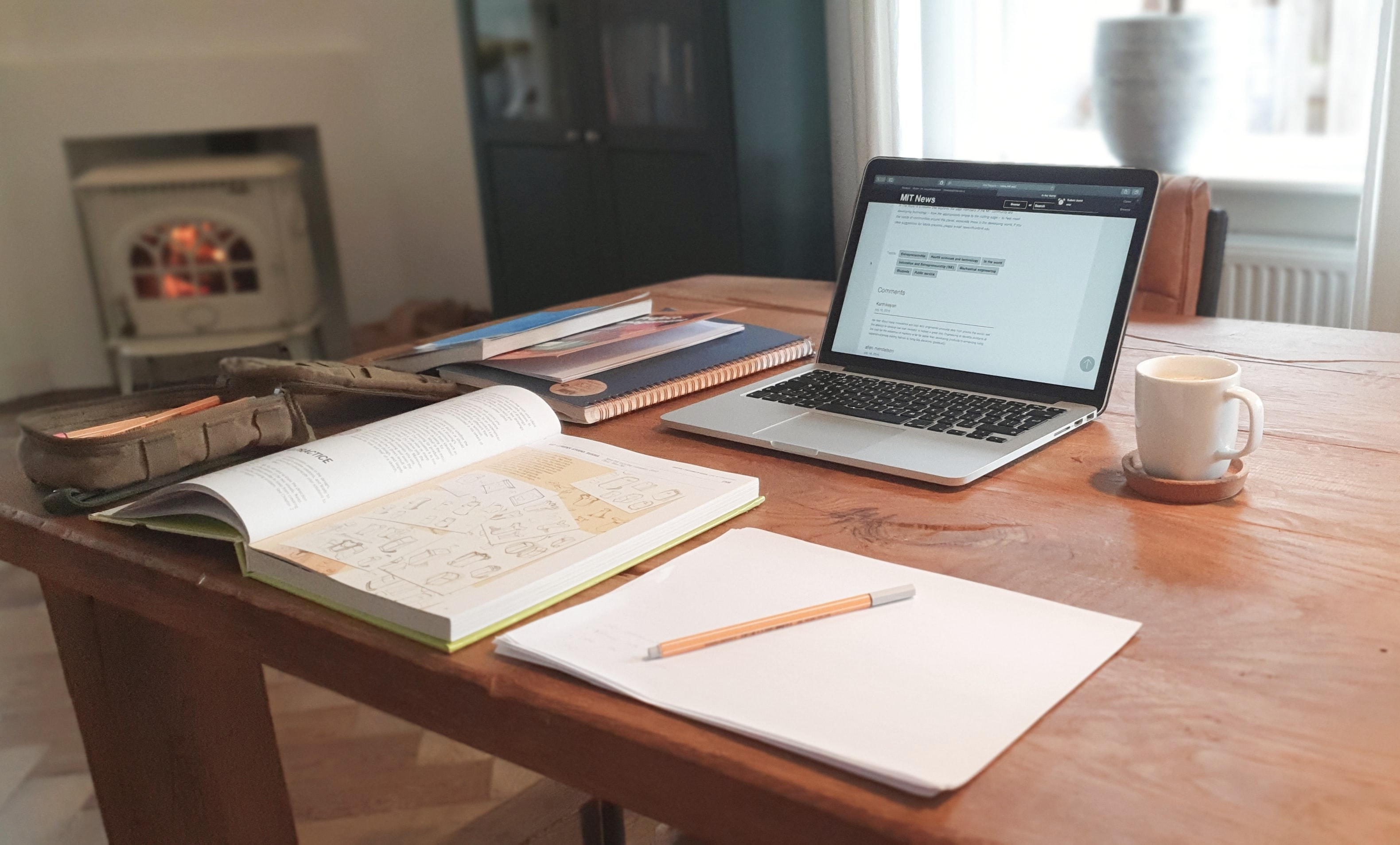 An open desk has a few journals and a laptop. Journaling is an excellent way to reflect and build gratitude.