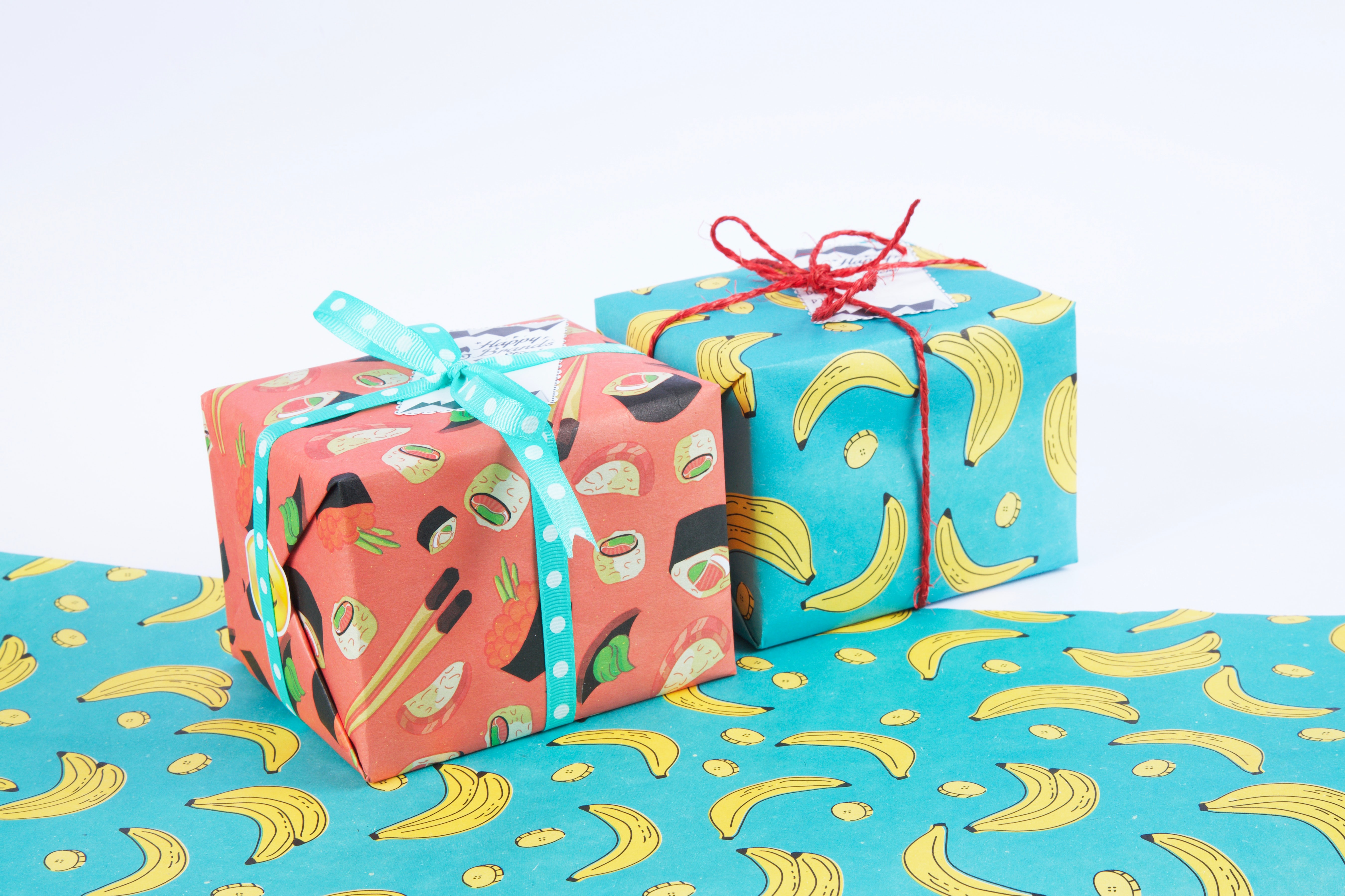 Food-based wrapping paper covers two gifts. Gifts are a great way to recognize remote teammates.