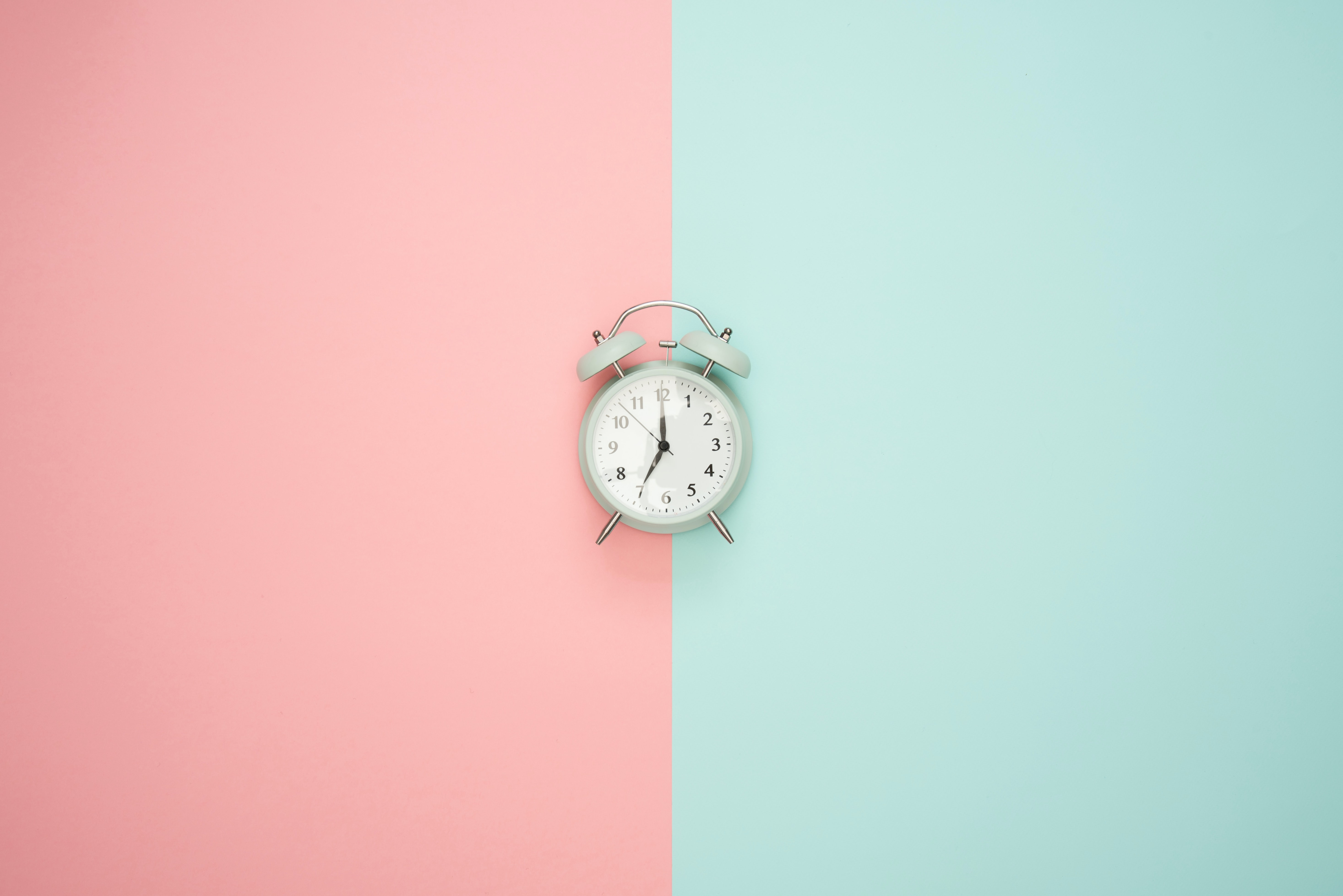 A pink and blue background is split by a clock. Employee engagement isn't limited to timezones.