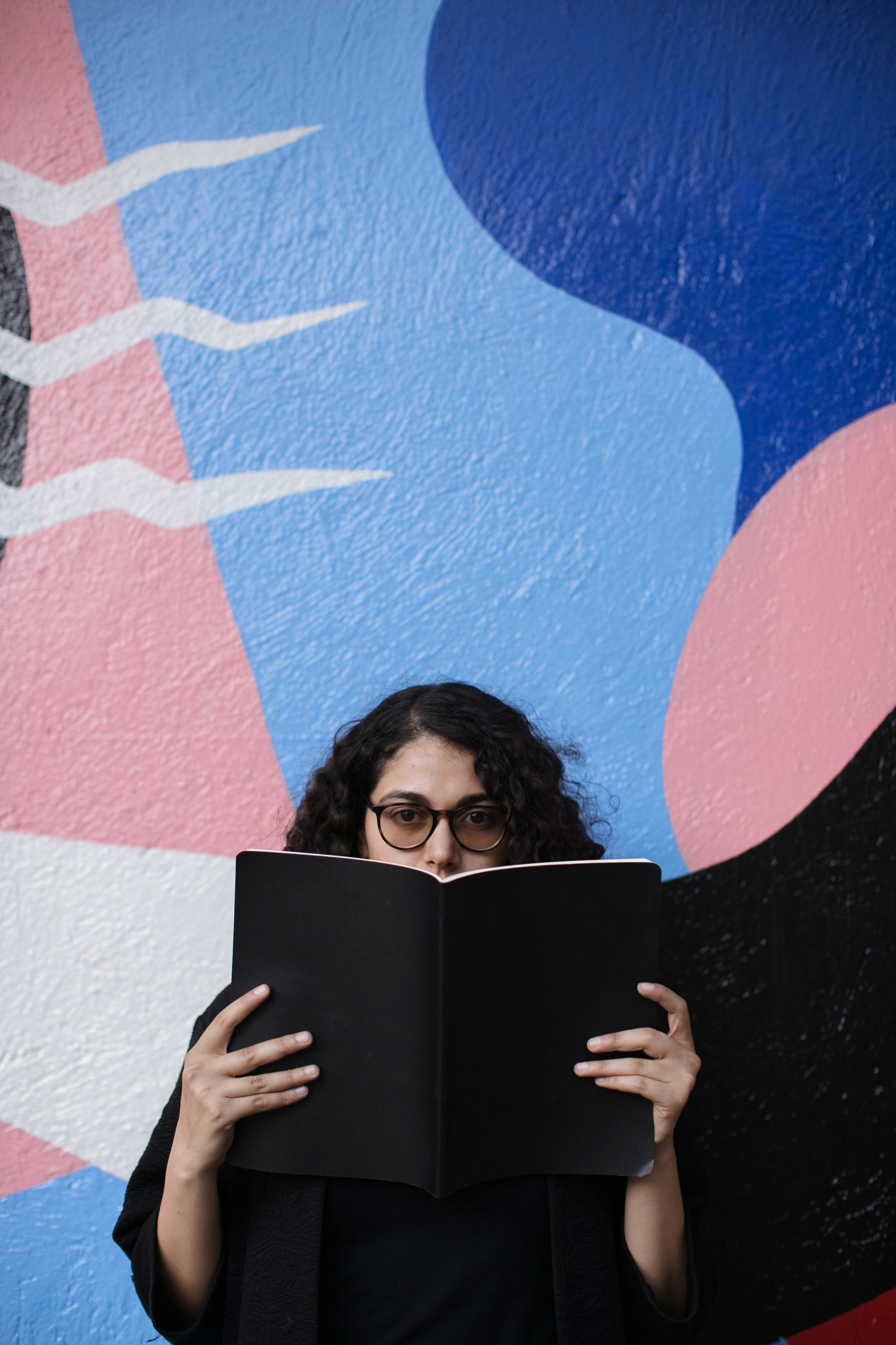 An annoyed woman reads a book in front of a large colorful mural.