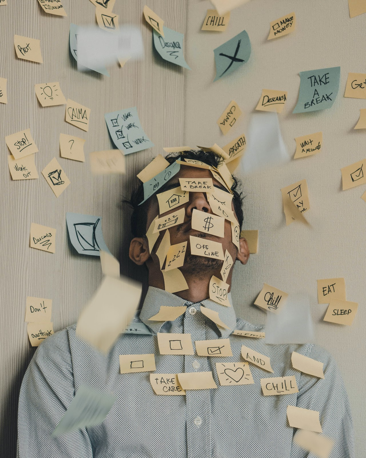 Burnout is all too real in pandemic work-from-home. This image shows an exhausted man covered in to-do post-it notes.