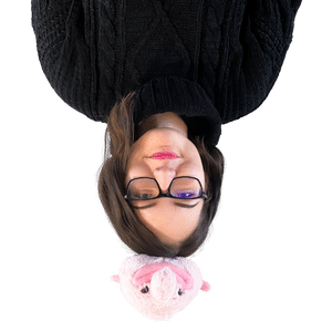 The founder Elina upside down with a blob-fish plushy on her head.