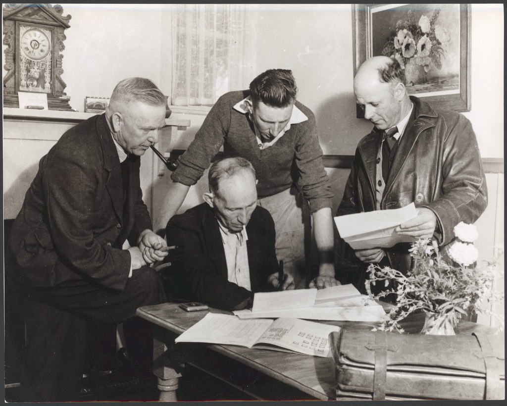 Four men leaning over a table reading some papers