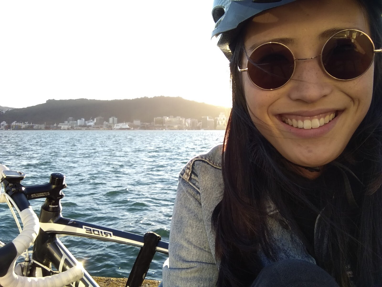 Jenny Sahng with a bike with a view of Wellington harbour