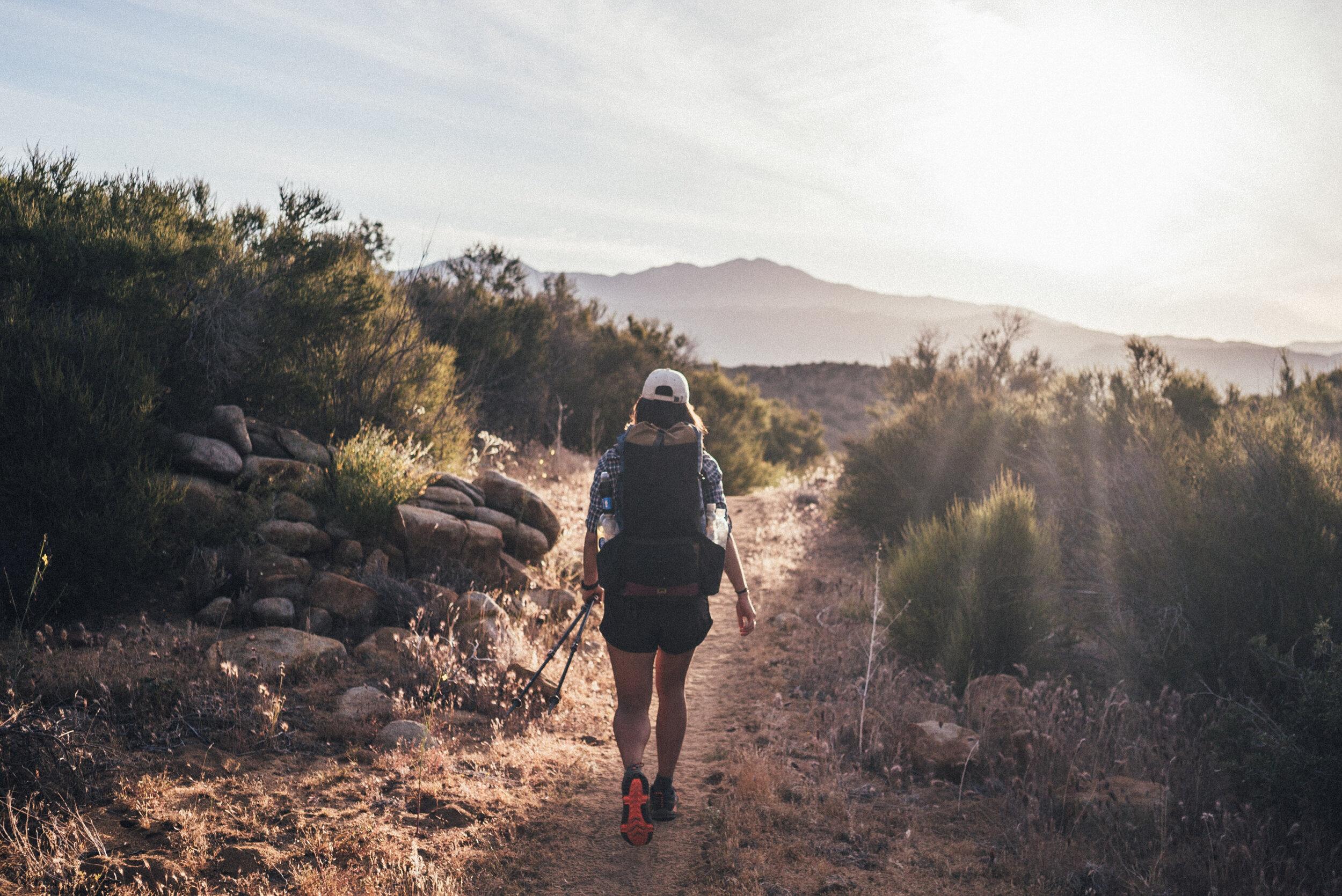 Elina hiking through a desert on PCT