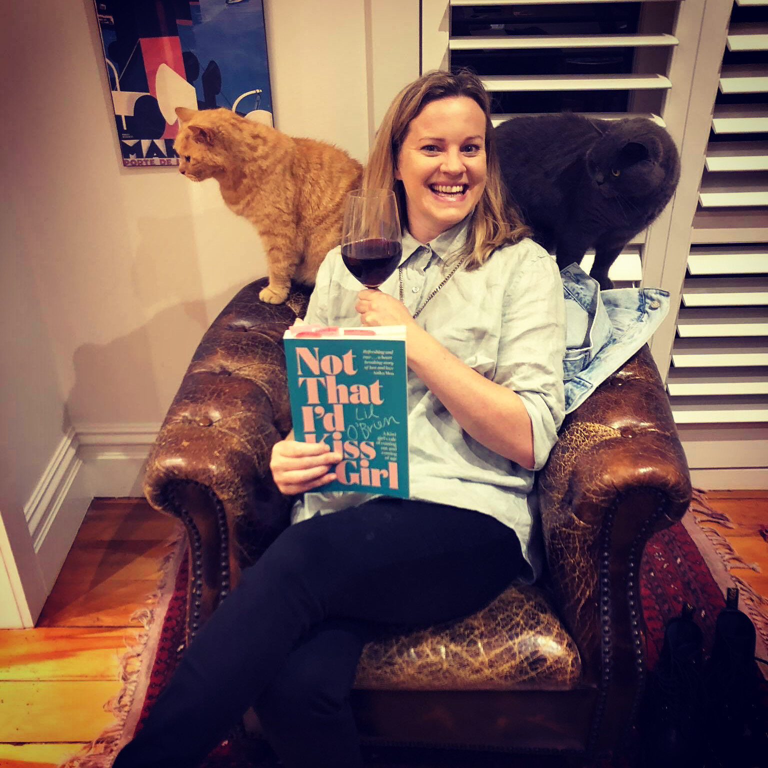 Lil in a big arm chair with a glass of wine, her book and cats flocking around, just before the book launch