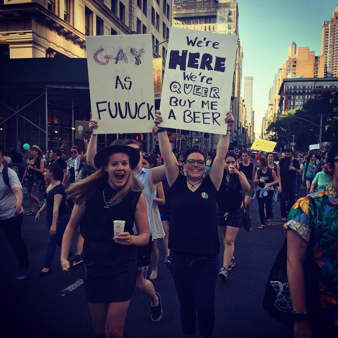 "Photo from Lil's favourite event of the NYC calendar, the Dyke March. back in 2016/17. People are holding posters that say ""Gay as fuuuuck� and ""we're here we're queer buy me a beer�"