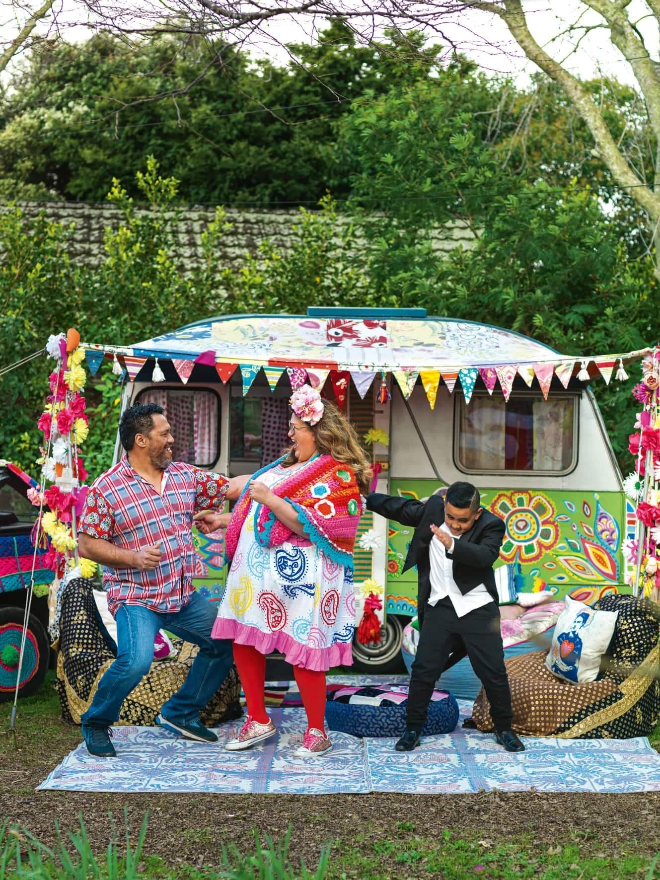 Rudi, Lissy and her grandson Christian dancing in front of their very colourful caravan, photo cred: Jane Ussher from NZ Life and Leisure